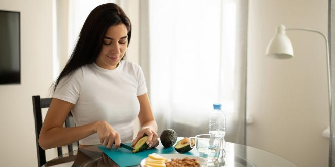 a woman cutting up avocado for a keto-friendly snack